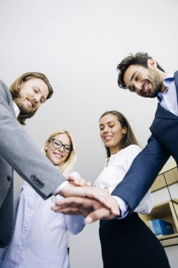Closeup of young coworkers putting hands together as symbol of unity in the office