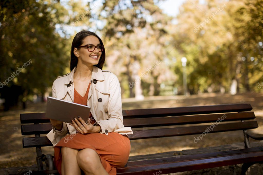 Woman sitting on bench in park during autumn weather using tablet pc and  checking social media.
