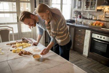 Loving couple preparing pasta in the rustic kitchen