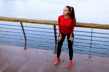 Pretty young woman takes a break after running in urban area