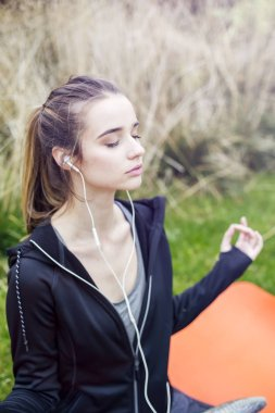 Young woman listening music and doing yoga zen pose on the grass