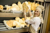 Pretty young woman selling fresh bread in the bakery
