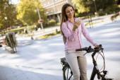 hübsche junge Frau mit Elektrofahrrad und Mobiltelefon im städtischen Umfeld