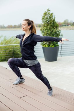 Fit young woman with earphones doing stretching exercises on urban stairs outdoors