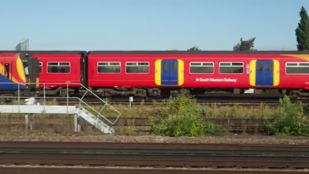 LONDON, UK - CIRCA SEPTEMBER 2019: A South Western Railway train - seen from a moving train - passes behind another stopped train