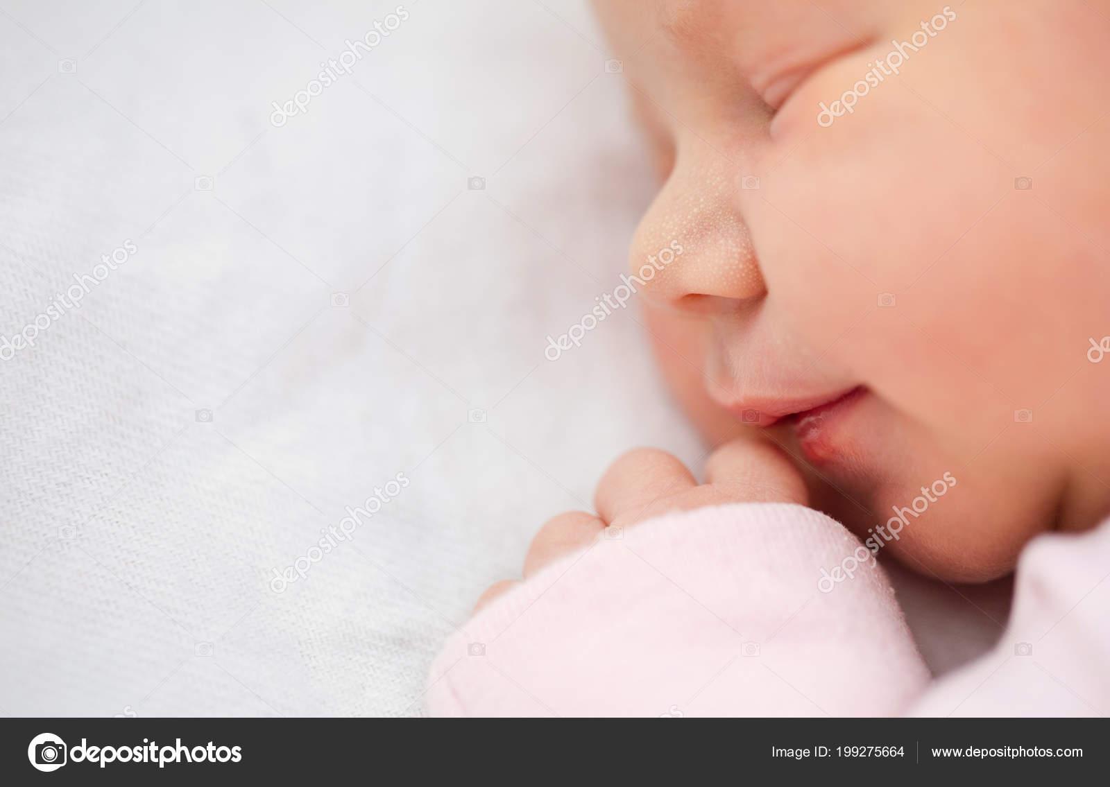 Closeup newborn baby girl beautiful one day old girl smiling stock photo