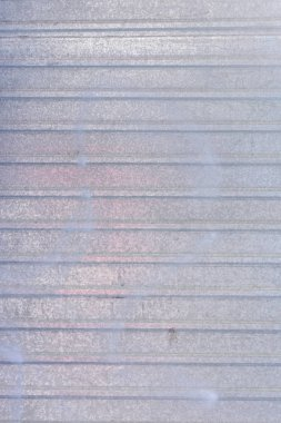 Wall of sheet metal. Blank background with colored gray overflows. Texture of corrugated metal.