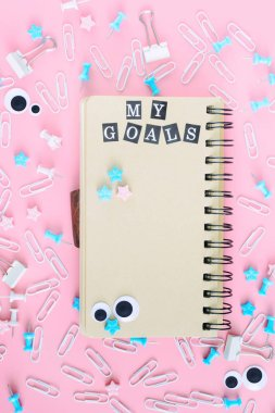 A notepad with brown pages lies in the center of the clutter of office supplies. In the notebook there is an inscription My Goals from white letters on black squares. Beautiful picture on a pink background.