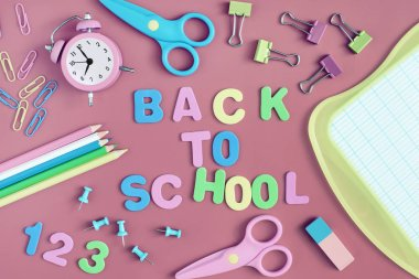 On a pale red background, school and office supplies are chaotically arranged. In the center is the inscription BACK TO SCHOOL, made in multi-colored letters. Beautiful pictures on top, layout.