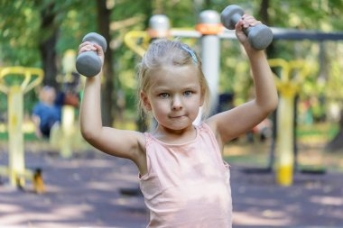 little girl with blond hair going exercises with dumbbells
