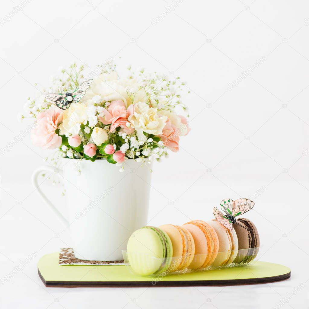 flowers in a cup and macaroons on a plate