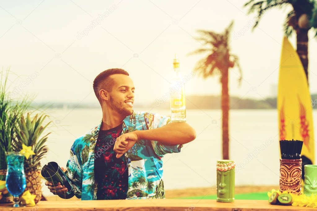 Handsome smiling Latin American bartender standing near the bar