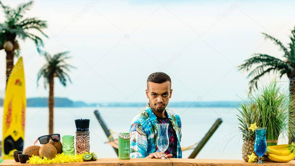 Handsome Latin American bartender standing near the bar counter