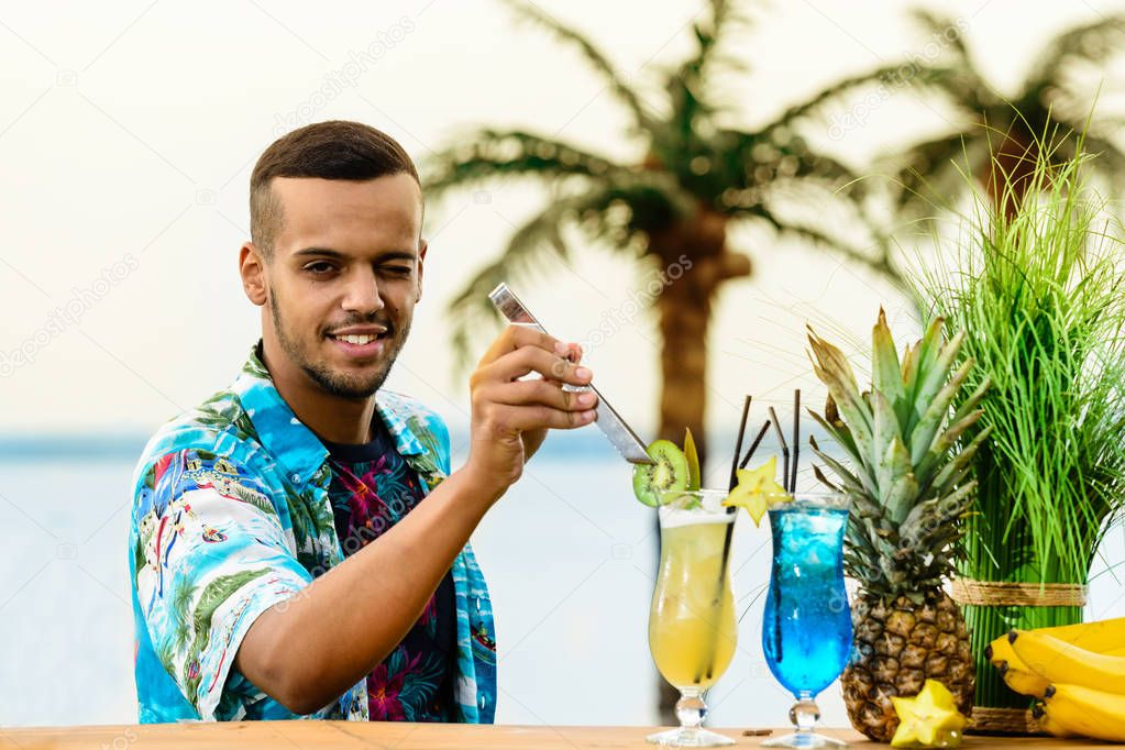 Handsome Latin American bartender standing near the bar counter,