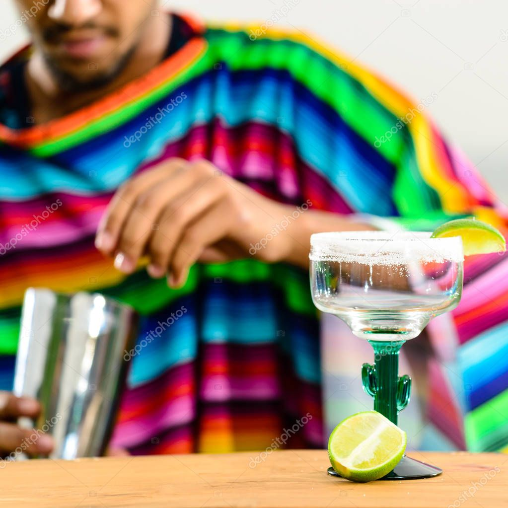 Selective focus on glass with fresh lime lemonade on a bar count