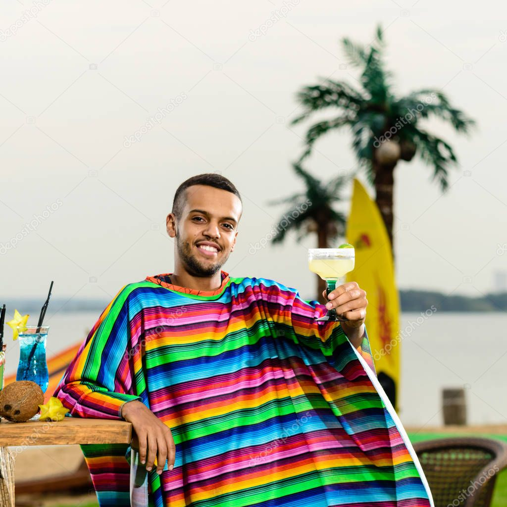 Selective focus on handsome, smiling Mexican bartender standing