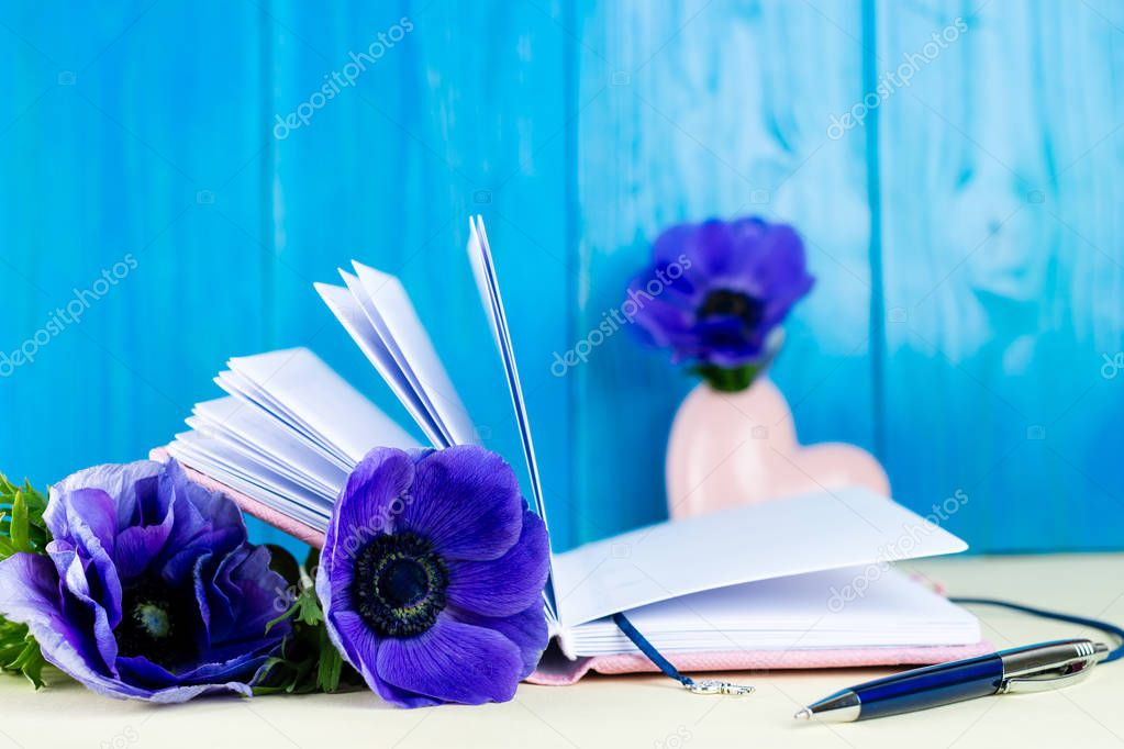 Pink notebook, pen and blue Anemone flowers. Concept of planning