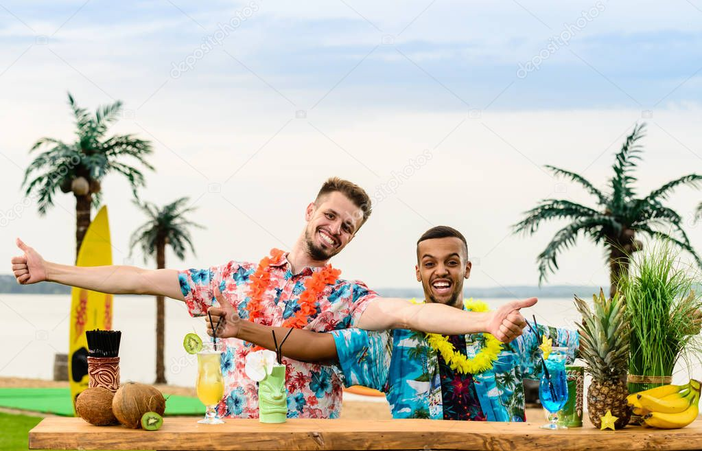 Handsome caucasian bartender and Latin American barman standing