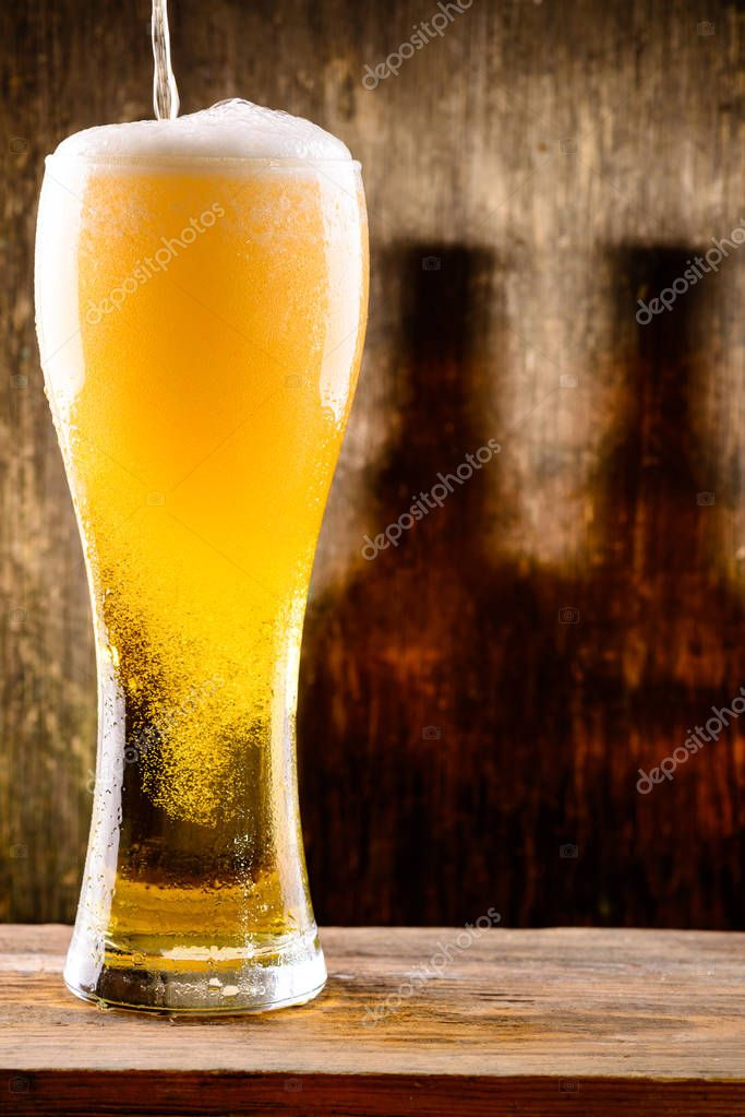 Fresh cold light beer pouring into glass with drops of water on