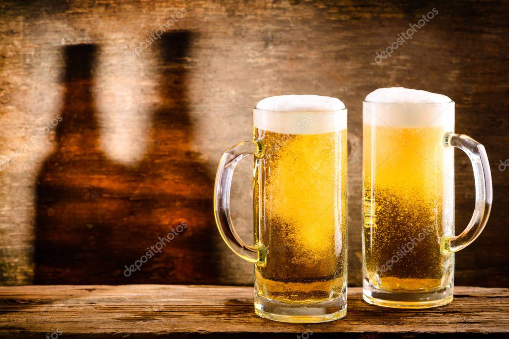 Two fresh cold light beer in a beer mug with foam and drops of w