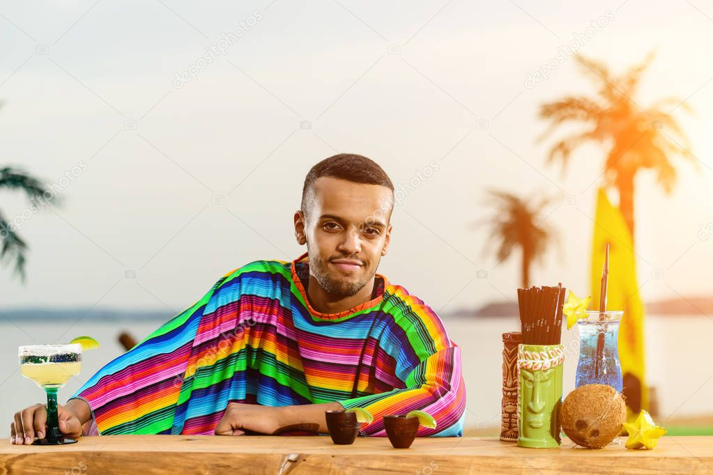 Front view of handsome positive Mexican bartender standing on th