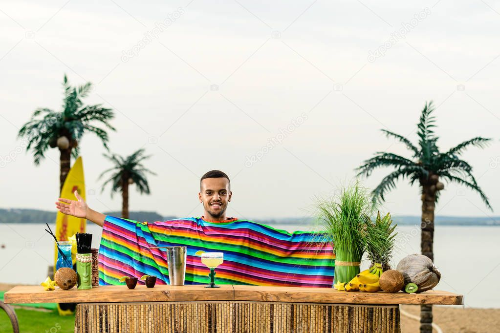 Front view of handsome, smiling Mexican bartender standing near