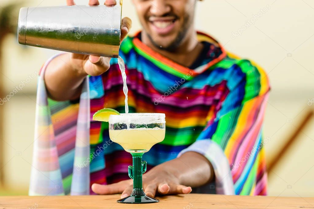 Close-up of handsome, smiling Mexican bartender standing on the