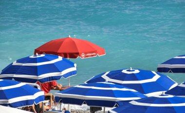 red lifeguard sunshade beach board among blue umbrellas