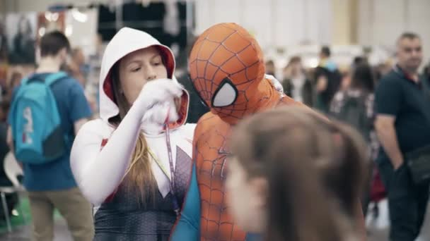 POZNAN, POLAND - MAY 19, 2018. Young woman helps man to wear Spiderman cosplay costume