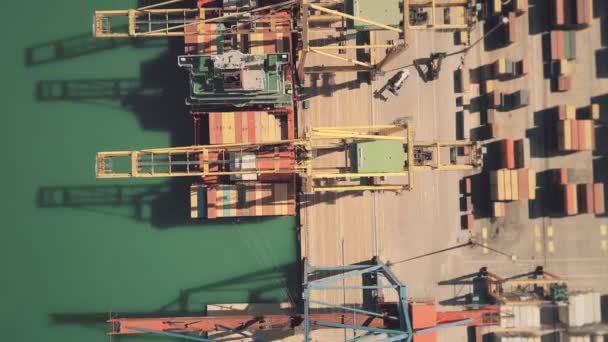 Aerial top down view of big cargo ship being unloaded at seaport container  yard