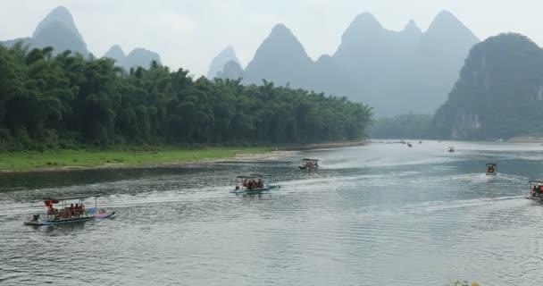 Malebný pohled na plachetnici podél řeky Li mezi zelenými lesy a krasovými horami v Yangshuo County Guilin, Čína. Yangshuo je oblíbenou turistickou destinací z Asie.