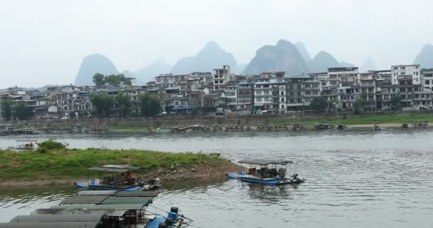 Scenic view of sailing boat along the Li River among green woods and karst mountains at Yangshuo County of Guilin, China. Yangshuo is a popular tourist destination of Asia.