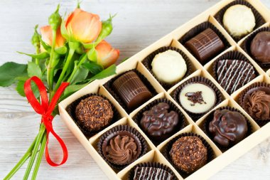 beautiful gentle orange roses and sweet chocolate candies in box on wooden surface