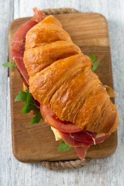 croissant with argugula, jamon, cheese and tomato on wooden surface