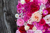 Photo pink,red, violet and white roses on wooden surface