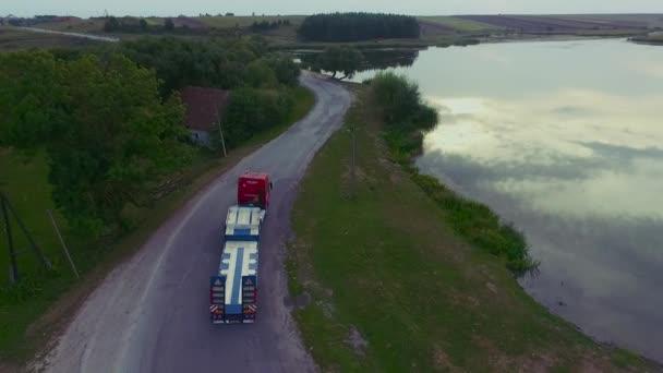 Letěl vysoko nad částečně truck nákladní přepravu zboží na rušné silnici po celé zemi v krásný letní večer. Provoz, řízení a zrychlení na rušné dálnici na golden sunset