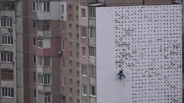 Höhen-Arbeit. Der Mann arbeitet auf Hochhaus Werke Verkleidung, Verputzen des Hauses. Erwärmung der Fassaden der Hochhäuser. Erwärmung der Fassaden der Hochhäuser. Höhen-Arbeit in einem Wohngebiet. Erwärmung der Häuser.