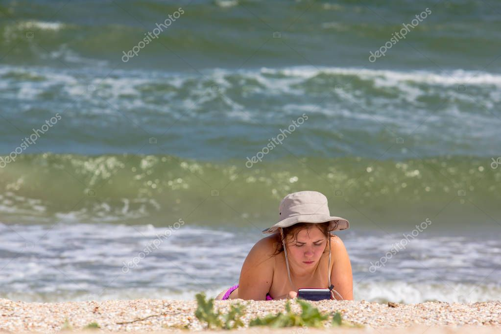 young woman reading an ebook on the beach lying on the sand