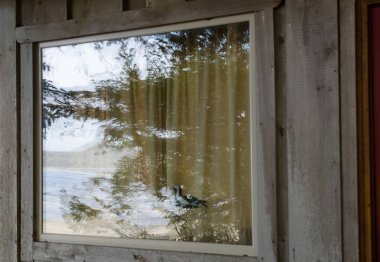 Reflections of Chesterman Beach in the windows of a cabin