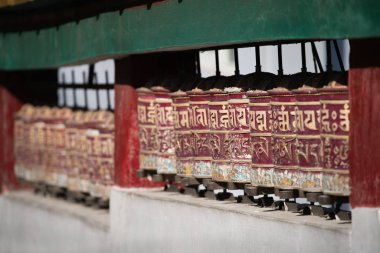 Holy tibetan prayer wheels arrange in row for people rolling in temple
