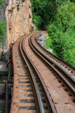 Old railroad tracks on bridge beside cliff rock