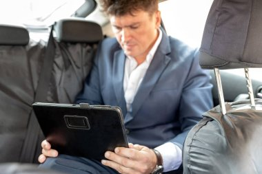 Businessman working on tablet and smartphone inside car on bright day