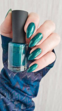beautiful female hand with stylish manicure and bottle with nail polish , closeup