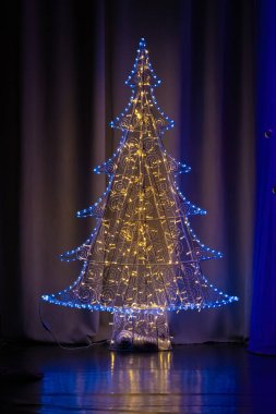 Christmas tree with colorful garland on the stage, without people