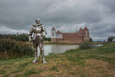 knight in metal armor posing near castle, medieval culture