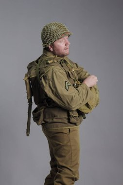 Man actor in the movie role of an old military man posing against grey background