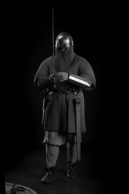 portrait of a brutal bald-headed viking in battle mail  posing against a black background. Early medieval period