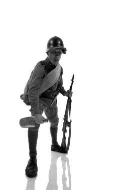 Male actor in uniform of ordinary soldier of Russian army during the Second World War posing against white background in studio