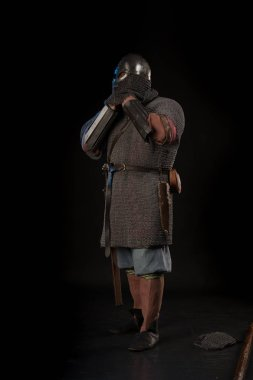 portrait of a brutal bald-headed viking in battle mail with a battle ax in hands posing against a black background. Early medieval period