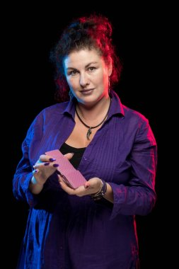 woman in purple clothes holds a deck of cards and shows tricks in a scenic light.